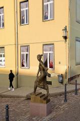 Bronzeskulptur junge Frau auf einer Treppe in der Straße Schlossberg von Gotha; leer stehendes Wohnhaus mit Trompe-l'œil Malerei /  illusionistische Darstellung von Menschen im Fenster.