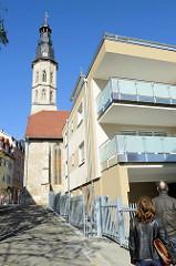 Modernes Wohngebäude mit Balkon, im Hintergrund der Kirchturm der Allerheiligenkirche in Mühlhausen.
