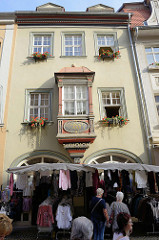 Verkaufsstand mit Kleidungsstücken in der Herrenstraße von Naumburg, dahinter ein Bürgerhaus - erbaut 1525.