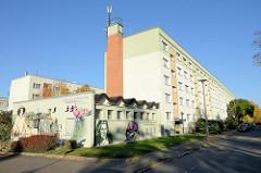 Heizwerk Dichterweg der Stadtwerke Weimar, poetische Fassadenmalerei am Zweckbau - dahinter mehrstöckige Wohnblocks.