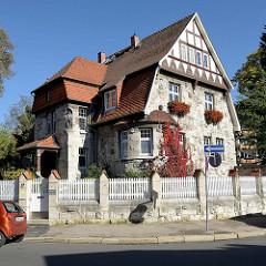Villa im Heimatstil -  geschnitzte Dekorelemente im Giebel, Steinfigur eines Holzarbeiters mit Axt und Säge beim Eingang des Gebäudes; Architekturbilder aus Mühlhausen/Thüringen.