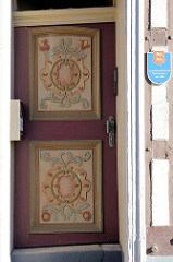 Mit farbigen Schnitzereien geschmückte Eingangstür eines ehem. Landsknechtshaus in Duderstadt; Architektur / Baustil der Renaissance um 1600.