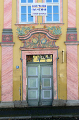 Historische Eingangstür am Untermarkt in Mühlhausen; farbenprächtiges Portal mit goldenem Monogramm und Wappen.