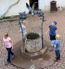 Schmiedeeiserner Brunnen mit Drachendarstellung im Burghof der Wartburg bei Eisenach.