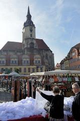 Wochenmarkt auf dem Marktplatz von Naumburg; Marktstände mit Taschen / Gürteln und Spitzengardinen; im Hintergrund der Kirchturm der Sankt Wenzel Kirche.