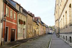 Straße mit Kopfsteinpflaster und Wohnhäusern mit unterschiedlich farbiger Fassade in der Schulstraße von Naumburg; rechts die gelbe Ziegelfassade der freien Schule im Burgenland Jan Hus.