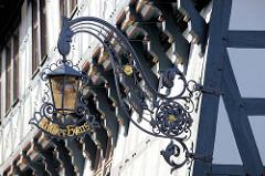 Verzierte eiserne Lampenhalterung mit der vergoldeten Inschrift Lutherhaus am Luttermuseum in Eisenach.