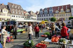 Wochenmarkt auf dem Marktplatz von Naumburg; Marktstände mit Gemüse und Taschen.