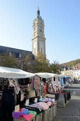 Marktgeschehen auf dem Marktplatz von Eisenach, Wochenmarkt mit Kleidung und Decken, im Hintergrund die Georgen Kirche.