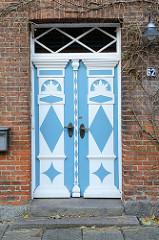 Alte Eingangstür mit blauweiß abgesetzten Schnitzereien in der Lübecker Straße von Bad Segeberg