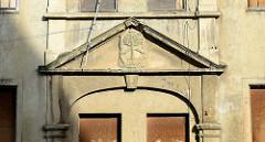 Leer stehendes Gebäude mit vernagelten Fenstern und Türen, Portal mit Relief / Lebensbaum und Reste einer Fassadenaufschrift.