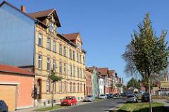Wohnhäuser in der Tonbergstraße von Mühlhausen; Wohnblock mit gelber Ziegelfassade roten Ziegelbändern; die Dachmansarde ist mit Fachwerk versehen.