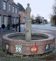 Zunftbrunnen in der Fußgängerzone von Bad Segeberg; angefertigt mit den 14 farbigen Reliefs  / Handwerkswappen der Stadt.