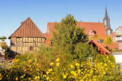 Historischer Fachwerkspeicher - blühende Herbstblumen; Türme und Dach vom historischen Duderstädter Rathaus - eines der ältesten Rathäuser Deutschlands - erbaut ab 1302.