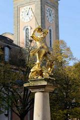 Goldene Brunnenfigur - Sankt Georg - am Georgsbrunnen in Eisenach. Im Hintergrund der Kirchturm der Georgen Kirche.