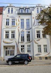 Hausfassade mit bunten Glasapplikationen / Mosaik Bänder, Entwurf Bildhauer Peter Fiedler - Haus voller Ideen in der Poststraße von Naumburg.