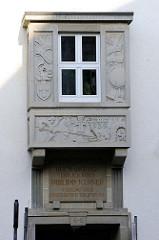 Erker mit Reliefdarstellungen und Spruchband: Gott grüß die Kunst - das Rechte verfechte; Verlagsgebäude der Eisenacher Tagespost, erbaut 1939