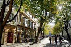 Blick in die baumbestandene Schillerstraße in der Altstadt von Weimar;  Touristen bummeln durch die Fußgängerzone.