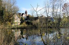 Blick über den kleinen Segeberger See; Wohngebäude am Seeufer, im Hintergrund der historische Wasserturm der Stadt Segeberg.