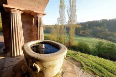 Blick auf den Park an der Ilm in Weimar; im Vordergrund Brunnen und dorische Säulen vom römischen Haus.