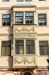 Erker mit buntem Blütenrelief und goldenen Bändern / Akanthusdekor am Naumburger Marktplatz - ehemalige Seifensiederei und Parfümerie.