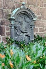 Bronzerelief der orgelspielenden hl. Caecilie als Schutzpatronin der Kirchenmusik am Bachdenkmal in Eisenach.