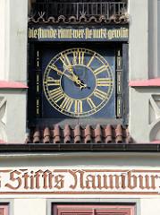 Uhr mit goldenen Zifferblättern an der Fassade vom Rathaus in Naumburg, goldene Aufschrift - die Stunde rinnt wer sie nutzt gewinnt.