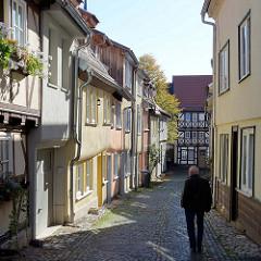 Schmale Kopfsteinstraße, Spiegelsgasse in Mühlhausen, einstöckige historische Wohnhäuser.