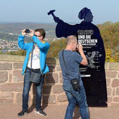 Aussichtsplattform auf der Wartburg bei Eisenach in Thüringen; Silhouette Martin Luthers mit Hammer nach einem Gemälde von Ferdinand Pauwels - Aufschrift Luther und die Deutschen / fotografierende Touristen.