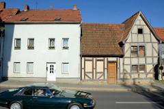 Altes leer stehendes Fachwerkhaus mit verrammelten Fenstern in der Johannesstraße von Mühlhausen; daneben ein kubischer Wohnblock mit kleinen Fenstern und glatt verputzter Fassade.