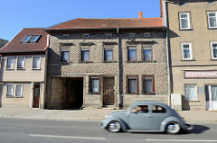 Altes Wohnhaus mit Toreinfahrt und Schindelfassade in der Wanfrieder Straße von Mühlhausen/Thüringen; ein alter Käfer/Volkswagen in rasanter Fahrt.