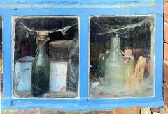 Scheunenfenster / Eisenfenster eines Schuppens in Seestermühe - Spinnweben und alte Flaschen.