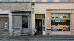 Gegensätze in Naumburg, Neue Straße - ein leer stehendes altes Lebensmittelgeschäft und ein Alcapone Pizzaservice mit bunter Werbung.