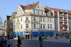 Mehrstöckige Geschäftshäuser am Neumarkt  / Lutherstraße in Gotha, rechts ein modernes Wohnhaus mit Balkons und Blumenkästen.
