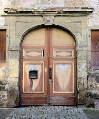 Altes Tor / Einfahrt mit Doppeltür aus Holz, verwaschene Firmenaufschrift einer Weinhandlung in der Neuen Straße von Naumburg.