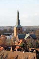 Blick über die Dächer von Bad Segeberg zum Kirchturm der Marienkirche; das Kirchengebäude wurde ab 1862 im neuromanischen Stil umgestaltet.