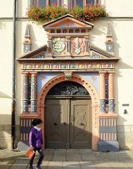 Renaissance-Portal vom Rathaus in Naumburg, farbige Säulen und Wappengiebel.