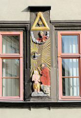 Religiöses Relief an der Fassades eines historischen Haus in Naumburg Darstellung Gottes, des Heiligen Geistes als Taube sowie Jesus Christus bei seiner Taufe durch Johannes; gespiegelte Inschrift.