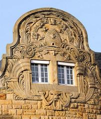 Geschäftshaus mit aufwändig dekorierten Stuckgiebel, Jugendstil / Art Nouveau; florale Bänder mit Bienenstock und emsigen Bienen als Symbol von Fleiß und Ordnung.
