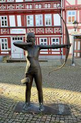 Bronzeskulptur Frau mit Pfeil und Bogen, Teil des Schützenbrunnens in Duderstadt; Inschrift ludimus non laedimus = Wir spielen, aber verletzen nicht. Bildhauer R. Pabel 1997.