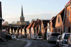 Einzelhäuser / Wohnhäuser mit Satteldach oder Krüppelwalmdach in der Lübecker Straße von Bad Segeberg. Im Hintergrund ragt der Kirchturm der Segeberger Marienkirche empor