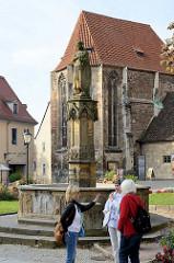 Ekkehard-Brunnen und die Dreikönigskapelle vor dem Naumburger Dom St. Peter und Paul. Der Brunnen nimmt Bezug auf den Markgrafen Ekkehard (etwa 985 bis 1046), die Brunnenanlage wurde um 1530 errichtet, der Standbild 1858 hinzugefügt.