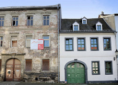 Alt und neu, Architekturgegensätze Naumburg - heruntergekommenes, leer stehendes Mietshausmit renovierungsbedürftiger Fassade, daneben ein fertig restauriertes Gebäude mit lackierter Toreinfahrt.