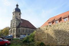 Ruine einer alten Steinmauer, Wildkraut - im Hintergrund die St. Othmar Kirche in Naumburg.  Das Kirchengebäude wurde im Stil des Frühbarock 1699 fertig gestellt.