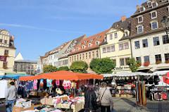 Wochenmarkt auf dem Marktplatz von Naumburg; Marktstände mit Taschen / Gürteln und Kleidung; am Rande des Marktes historische Wohnhäuser / Geschäftshäuser.