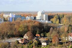 Blick vom Segeberger Kalkberg zu den Gebäuden der Segeberger Kliniken, die hoch aus den herbstlichen Bäumen herausragen.