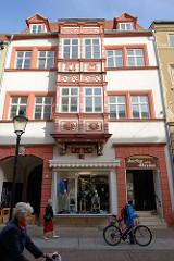 Historisches Geschäftsgebäude in der Jakobsstraße von Naumburg; Erker mit Stützfiguren und farblich abgesetzten Schmuckwerk.