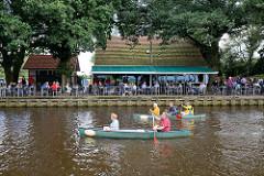Kanufahrt auf der Hamme bei Worpswede, am Ufer ein Café / Restaurant mit Biergarten.