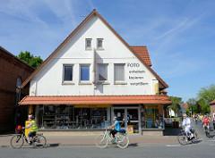 Wohn- und Geschäftshaus an der Hauptstraße in Burhave; Gruppe von Fahrradfahrerinnen -- Fassadenaufschrift  Foto entwickeln kopieren vergrößern.