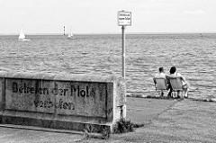 Betreten der Mole verboten, Aufschrift an der Molenmauer - Schild betreten auf eigene Gefahr; ein Pärchen sitzt auf Campingstühlen an der Mole von Wilhelmshaven und blickt aufs Wasser.